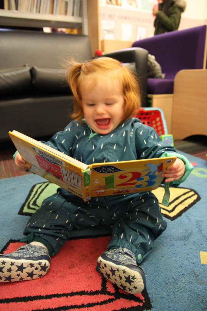 Baby grinning while reading a board book