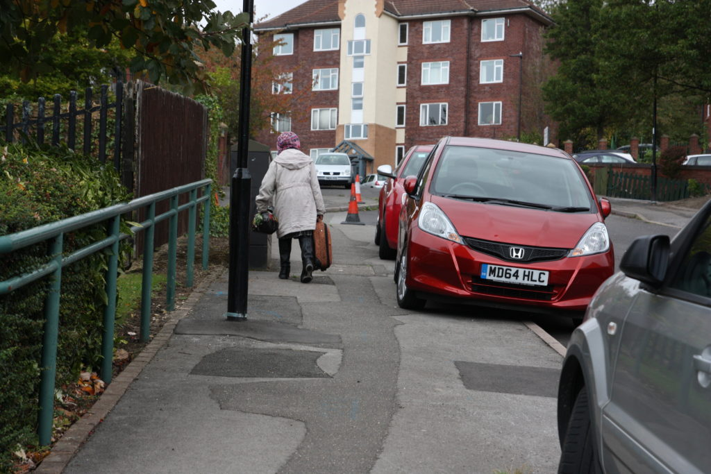 Woman with shopping walking on pavement obscured by parked cars