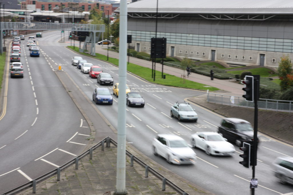 Large road with traffic, with man doing a wheelie on a bike alongside