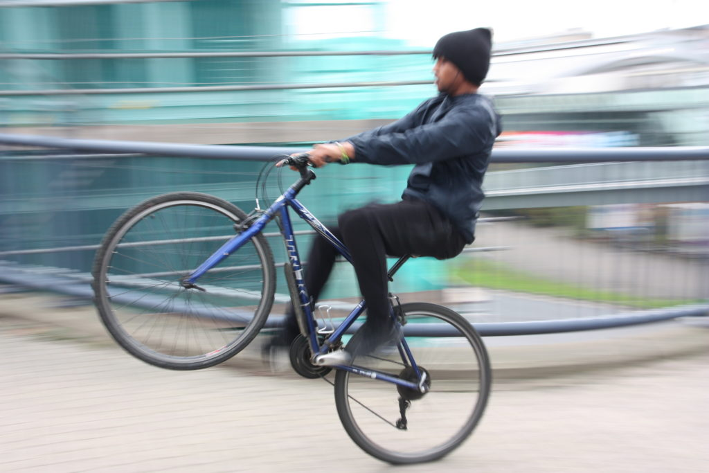 Man pulling a wheelie, with motion blur background